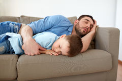 Happy father and son sleeping on sofa at home. Family, childhood, fatherhood, leisure and people concept - portrait of happy father and little son sleeping on Stock Photography