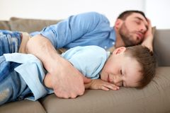 Happy father and son sleeping on sofa at home. Family, childhood, fatherhood, leisure and people concept - portrait of happy father and little son sleeping on royalty free stock photo
