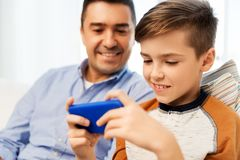 Happy father and son with smartphone at home stock image