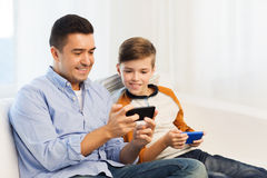 Happy father and son with smartphones at home Stock Photos