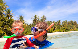 Happy father and son snorkeling on beach Stock Images