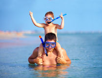 Happy father and son snorkeling stock photo