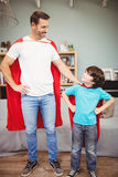 Happy father and son in superhero costume. While standing at home Royalty Free Stock Images