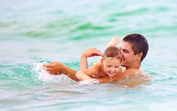 Happy father and son swimming in sea water Royalty Free Stock Photos