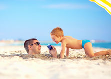 Happy father and son talking on smart phone together, on the beach Royalty Free Stock Photography