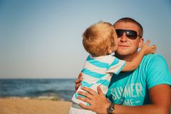 Happy father and son together at beach. Son is kissing his fathe. R Royalty Free Stock Photography