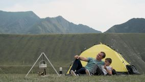 Happy father and son relax together and rejoice in front of the tent against the backdrop of the mountains. Happy father and son tourists relax together and stock video