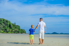 Happy father and son at the tropical beach, laughing and enjoing time together. Back view Royalty Free Stock Image