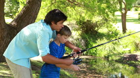 Happy father and son using a fishing rod Royalty Free Stock Images