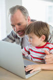 Happy father and son using laptop Stock Photo