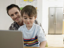 Happy Father With Son Using Laptop At Home Stock Photos