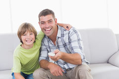 Happy father and son using remote control on sofa Royalty Free Stock Photo