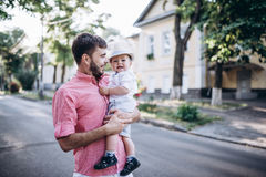 Happy father and son walk in old city street. City road with old bulding and green trees on the background Stock Photo