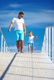 Happy father and son walking on blue sky horizon Royalty Free Stock Images