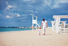Happy father and son walking on sandy beach, summer vacation Stock Photos