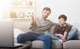 Happy father and son watching a movie on a laptop at home royalty free stock photos