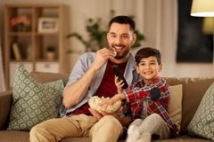 Happy father and son watching tv at home royalty free stock images
