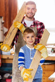 Happy father and son with wood plank at workshop Stock Photo