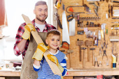 Happy father and son with wood plank at workshop. Family, carpentry, woodwork and people concept - happy father and little son carrying wood plank at workshop Royalty Free Stock Photos