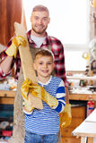 Happy father and son with wood plank at workshop. Family, carpentry, woodwork and people concept - happy father and little son carrying wood plank at workshop Stock Image