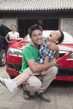 Happy Father and Son Wrestling outdoors in front of the car Royalty Free Stock Images