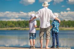 Happy father with sons on a fishing trip. On a beautiful lake royalty free stock images