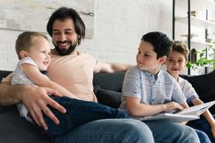 happy father and sons resting on sofa while reading book together royalty free stock photos