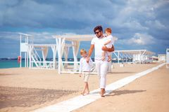 Happy father and sons walking on sandy beach, summer vacation in tropical resort Royalty Free Stock Photography