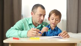 A happy father spends time with his son teaching and drawing with him. Dad and child draw with colored pencils, sitting