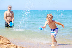 Happy father splashing water on laughing son Stock Photography