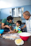 Happy father sprinkling flour on son hand while preparing food with grandfather. Happy father sprinkling flour on sons hand while preparing food with grandfather Royalty Free Stock Photos