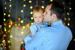 Happy father stick on hands small daughter. Happy father stick on hands small to the daughter, strong embraces and kisses. Bright festive fires on a background stock images