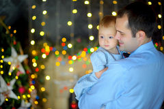 Happy father stick on hands small to the daughter. Strong embraces and together smile. Bright festive fires on a background. Waiting for a holiday royalty free stock photography