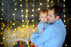 Happy father stick on hands small to the daughter. Strong embraces and together smile. Bright festive fires on a background. Waiting for a holiday royalty free stock images