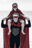 Happy father in superhero costume carrying son on shoulder Stock Image