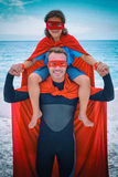 Happy father in superhero costume carrying son on shoulder Royalty Free Stock Photos