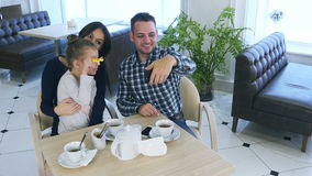Happy father takes selfie photo with his wife and daughter during their tea time in cafe or restaurant. stock footage