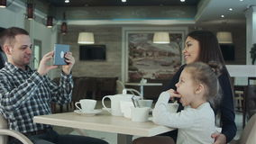 Happy father taking photo of his wife kissing their daughter by smartphone at restaurant. stock video footage