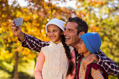 Happy father taking selfie with children at park. Happy father taking selfie with children against autumn trees at park Stock Photography