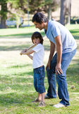 Happy father teaching baseball to his son. Happy father playing baseball with his son in the park Stock Photos