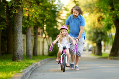 Happy father teaching his little daughter to ride a bicycle. Child learning to ride a bike. Stock Image