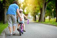 Happy father teaching his little daughter to ride a bicycle. Child learning to ride a bike. Royalty Free Stock Photography