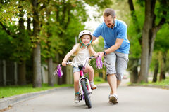Happy father teaching his little daughter to ride a bicycle. Child learning to ride a bike. stock images