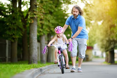 Happy father teaching his little daughter to ride a bicycle. Child learning to ride a bike.