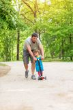 Happy father teaching his little daughter to ride kid scooter at the park royalty free stock images