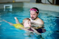 Happy father teaching his little daughter to swim. Active happy child learning to swim. Stock Images