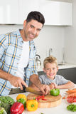 Happy father teaching his son how to chop vegetables Stock Photography