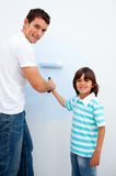 Happy father teaching his son how to paint Royalty Free Stock Image