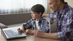 Happy father teaching his son to work on laptop computer at home, family care. Stock footage stock video