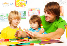 Happy father teaching kids to craft Stock Photo